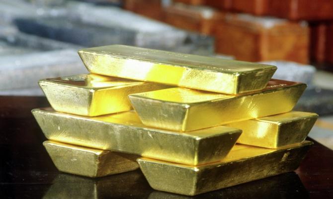 Золото слабо дешевеет из-за укрепления курса доллара